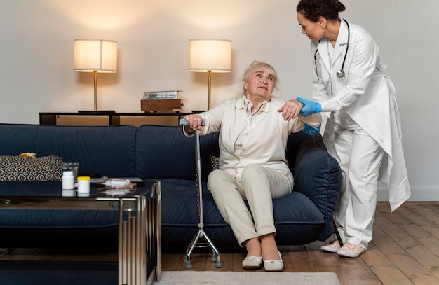 Doctor helping her old patient to stand up