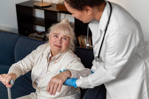 Medico che aiuta il suo vecchio paziente ad alzarsi in piedi