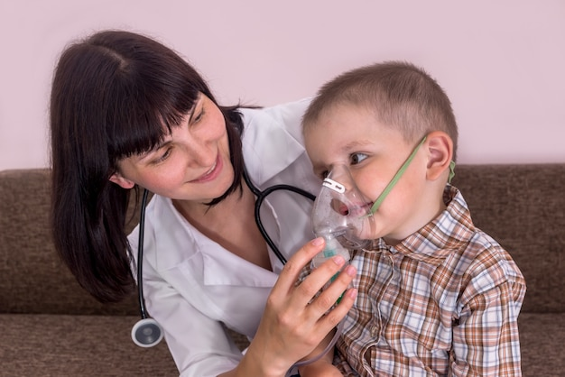 小さな患者が吸入用マスクを着用するのを手伝う医師