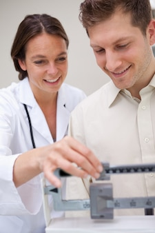 Doctor helping patient with adjusting scale