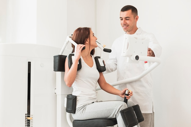 Doctor helping patient with medical work out machine