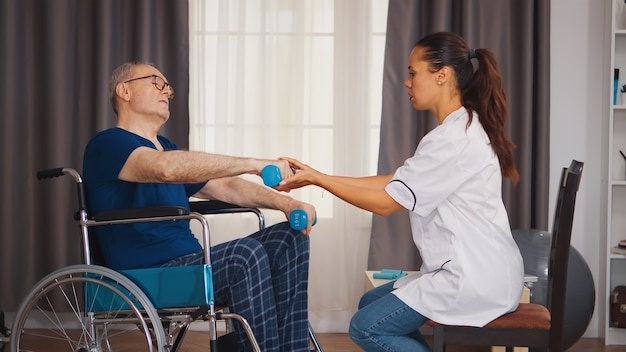 Doctor helping senior man in wheelchair with muscle rehabilitation exercise. disabled handicapped old person with social worker in recovery support therapy physiotherapy healthcare system nursing reti