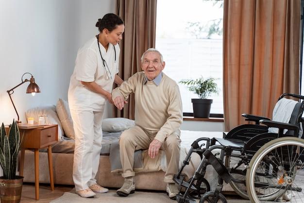 Medico che aiuta il paziente anziano