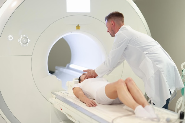 Doctor helping woman to lie down in mri machine in clinic correct positioning of patient during