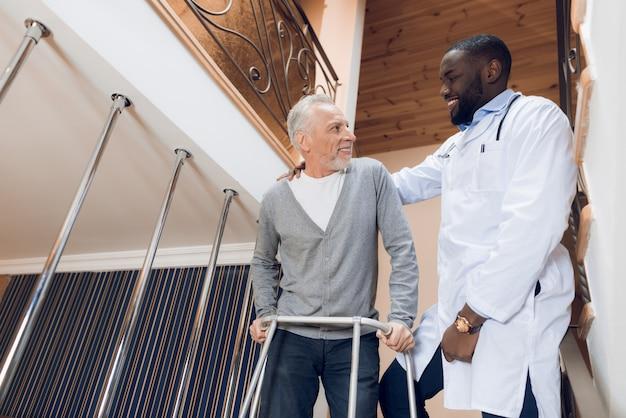 Доктор помогает мужчине спуститься по лестнице в дом престарелых.