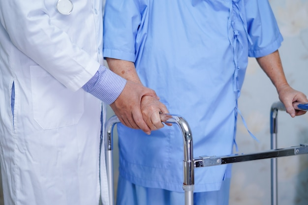 Doctor helps and cares asian people who uses walker in hospital