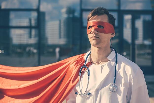 Доктор-герой в плаще, стоящий на городской улице.