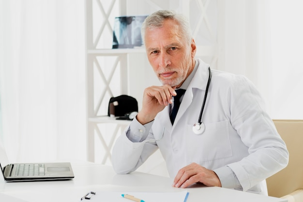 Doctor at his desk with hand on chin