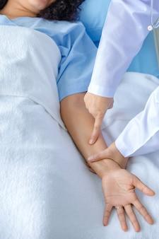 Врач держит руку пациента на кровати в больнице и проверяет нервную систему для лечения и лечения. понятие синдрома гийена-барре и болезни онемевших рук или побочного эффекта вакцины.