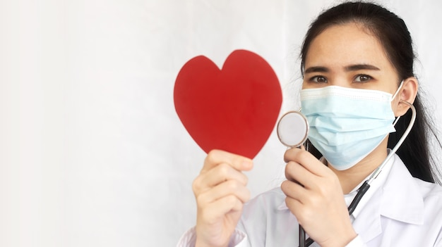 Doctor hold stethoscope check red heart , world heart day Premium Photo