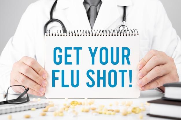 Get your flu shot、医療コンセプトでカードを持っている医師