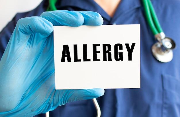 テキストアレルギーのカードを持っている医師。医療の概念。
