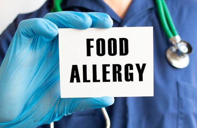 テキストのカードを持っている医師食物アレルギー