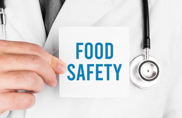 Доктор держит карточку с текстом безопасность пищи, медицинская концепция