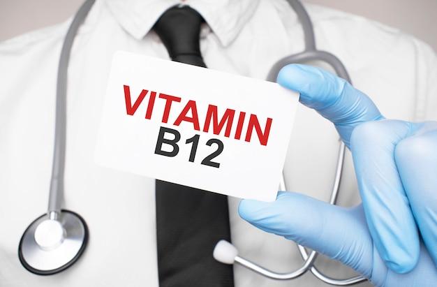 Vitamin b12、医療コンセプトのテキストが付いたカードを持っている医師