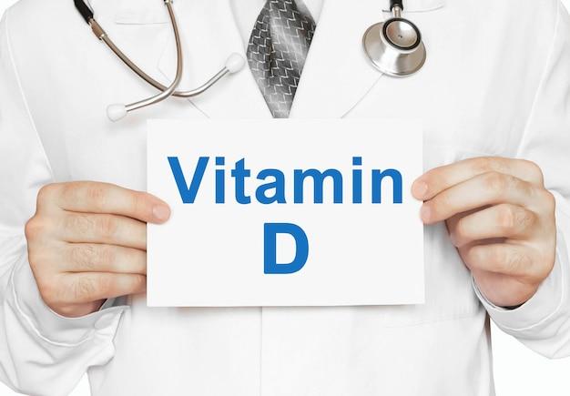 Доктор держит карточку с витамином d, медицинская концепция