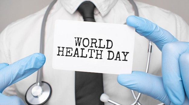 Врач держит карту с всемирным днем здоровья