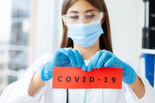 텍스트 covid-19와 종이 카드를 들고 의사.
