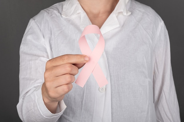 유방암과의 싸움의 핑크 리본 상징을 들고 의사.