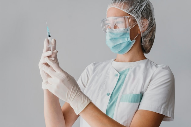 ワクチンの注射器を持っている医師