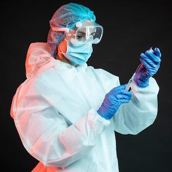 Врач держит шприц в медицинской маске