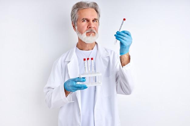 Врач держит пробирку с жидким раствором в лаборатории, готовит результаты