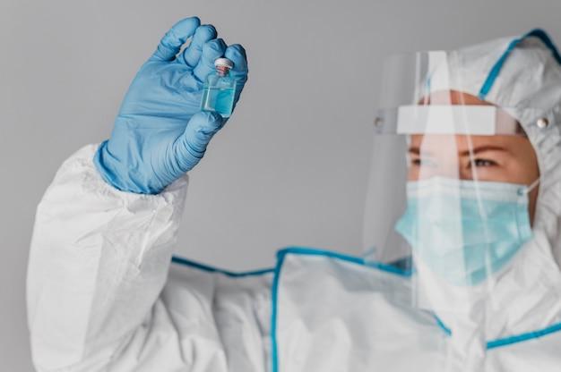 보호 장비를 착용하는 동안 백신 병을 들고 의사