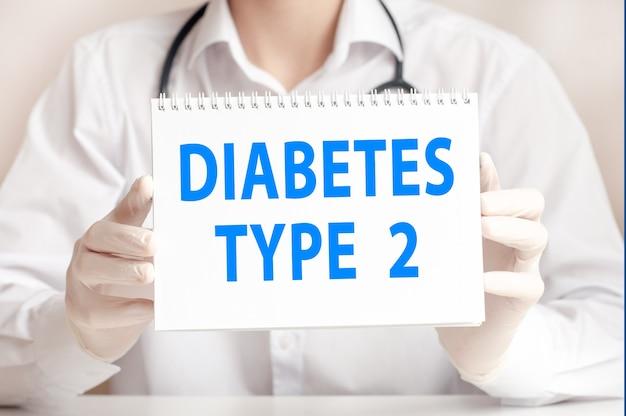 Доктор держит белую карточку в руках и указывает на слова диабет 2 типа