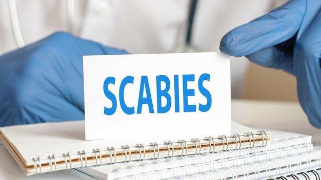 Доктор держит карточку белой бумаги с чесоткой текста.