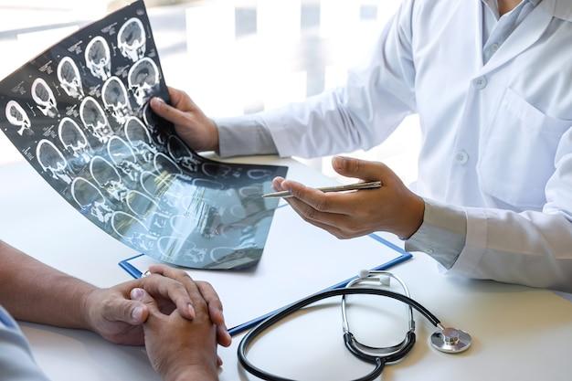의사는 환자의 ct 스캔으로 뇌를 검사하는 엑스레이 필름을 들고 보고 의료 문제를 설명하는 동안 결과를 분석합니다.