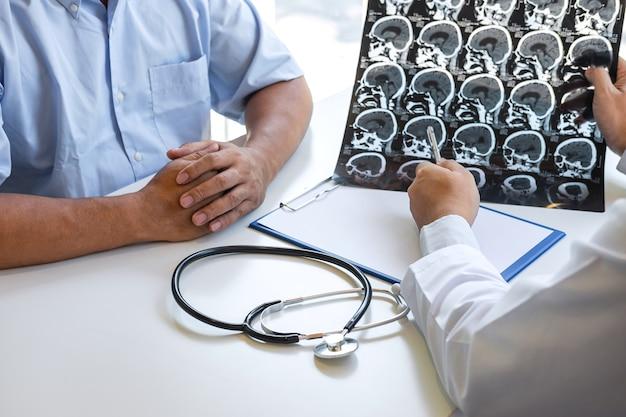 Доктор держит и смотрит на рентгеновский снимок, исследует мозг путем компьютерной томографии пациента и анализирует результат