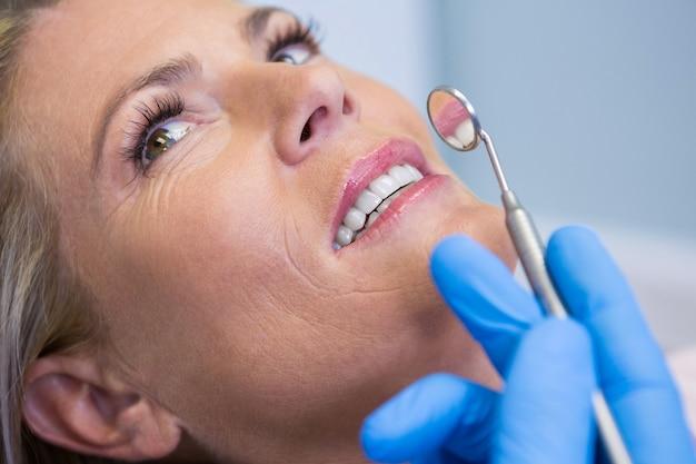 診療所で女性が斜めの鏡を持っている医師