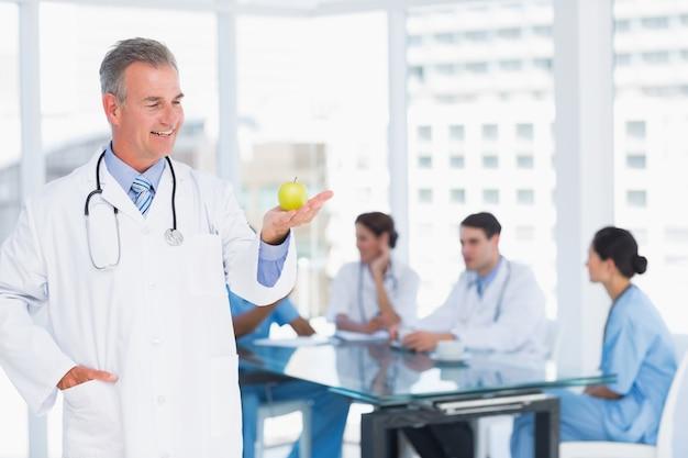 病院でテーブルの周りのグループとリンゴを持っている医師