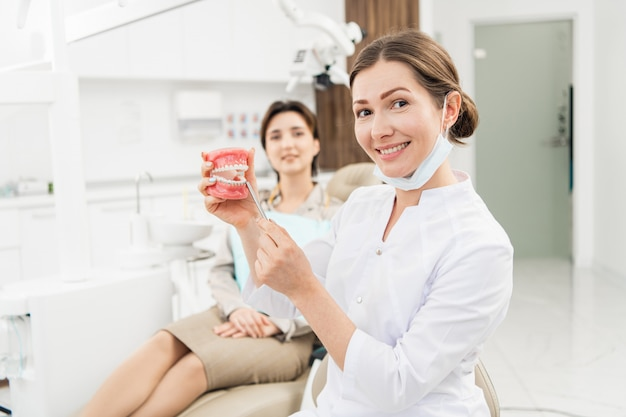 Doctor holding an artificial jaw with an orthodontic appliance