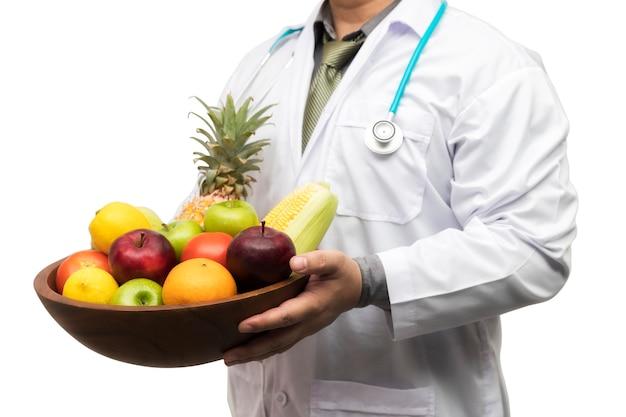 白で隔離のバスケットの品揃えの新鮮な果物や野菜を保持している医師