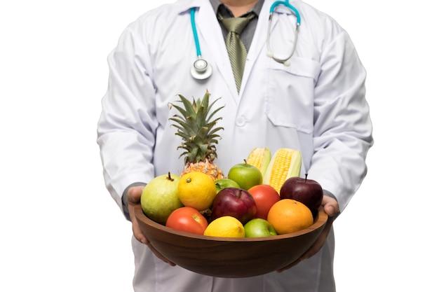 Доктор держит корзину ассорти свежих фруктов и овощей изолированы