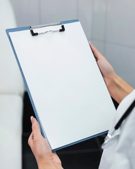 Doctor holding a blank clipboard