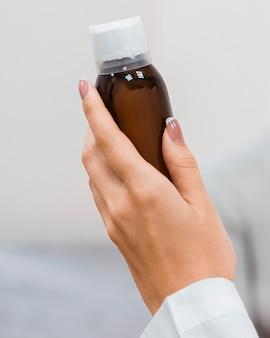 Medico che tiene una bottiglia di medicina
