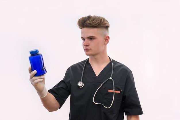 Доктор держит бутылку с таблетками, изолированными на белой стене