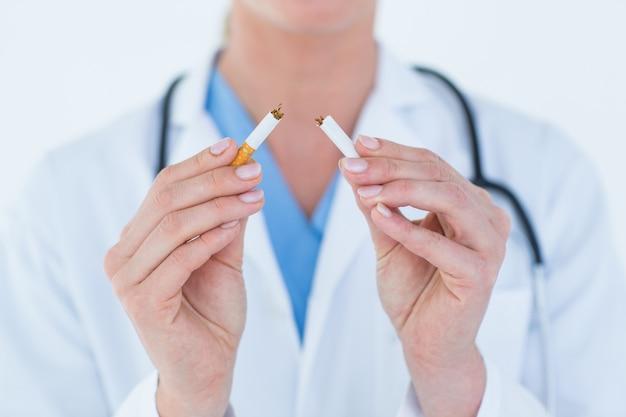 Doctor holding broken cigarette