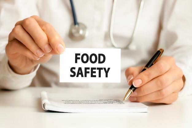 단어 식품 안전, 의료 개념으로 카드를 손에 들고 의사. 병원, 클리닉 및 의료 비즈니스에 대한 개념 의료.