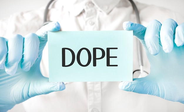 의사가 손에 카드를 들고 단어 dope를 가리키는