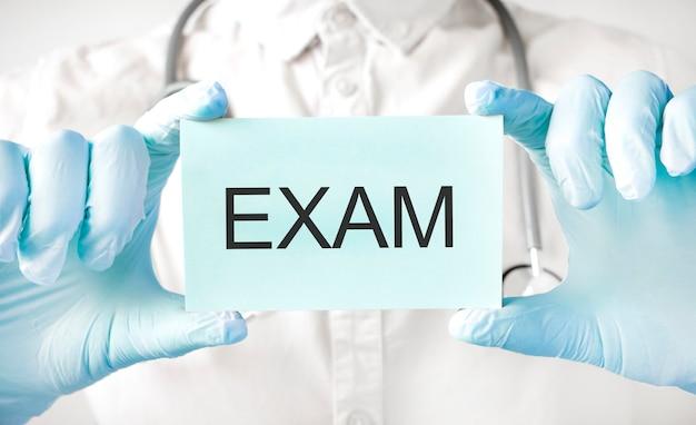 手にカードを持って、単語examを指す医師