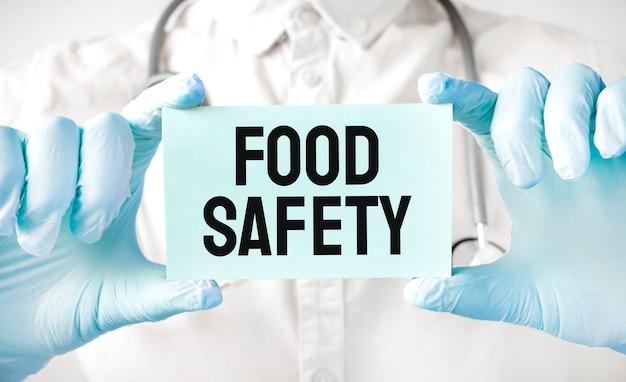 Доктор держит карточку в руках и указывая слово безопасность пищевых продуктов