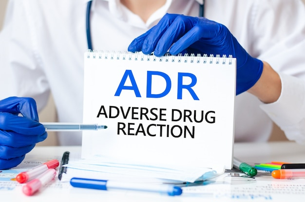 Doctor holding a card with text adr - short for adverse drug reaction, medical concept