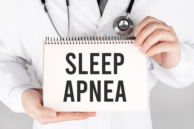 Doctor holding a card with text sleep apnea, medical concept