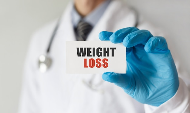 Doctor holding a card with text weight loss, medical concept