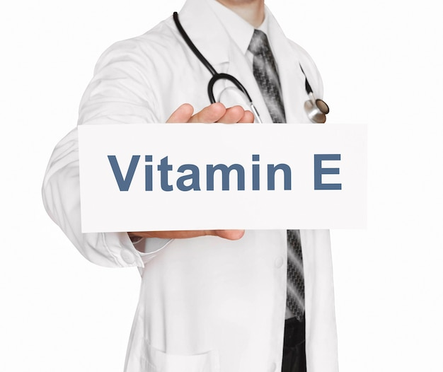 Doctor holding a card with vitamin e, medical concept