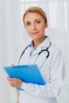 Doctor holding clipboard looking at camera