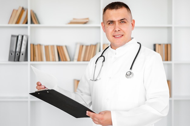 Doctor holding a clipboard and looking at photographer